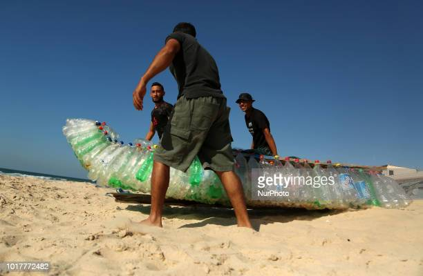Palestinian fisherman Mouad Abu Zeid ties his boat that he made of 700 Plastic empty bottles on a beach in Rafah in the southern Gaza Strip on August...