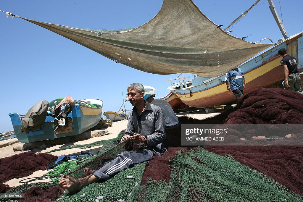 A Palestinian fisherman repairs his nets