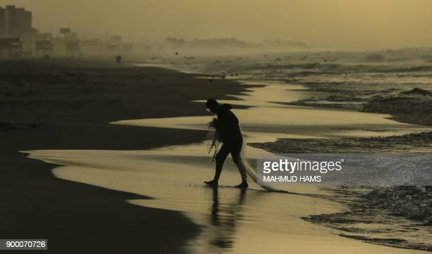 Palestinian fisherman walks with a fishingnet at the beach in Gaza City on December 31 2017 on the last day of the year / AFP PHOTO / MAHMUD HAMS