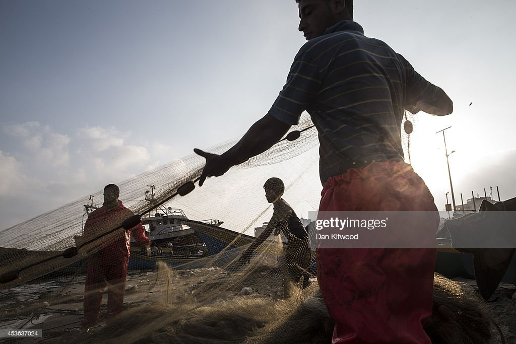Palestinian fishermen check their nets for fish after returning to shore after a mornings fishing on August 15, 2014 in Gaza City, Gaza. Recent restrictions imposed by neighboring Israel, has meant that their fishing boats are only allowed three nautical miles offshore, following a month of a complete ban on fishing during the recent fighting. A new five-day ceasefire between Palestinian factions and Israel went into effect yesterday as part of efforts aimed at reaching a permanent truce deal. The Palestinian death toll from Israel's weeks-long military onslaught on the Gaza Strip has risen to 1959, according to a Palestinian Health Ministry spokesman.