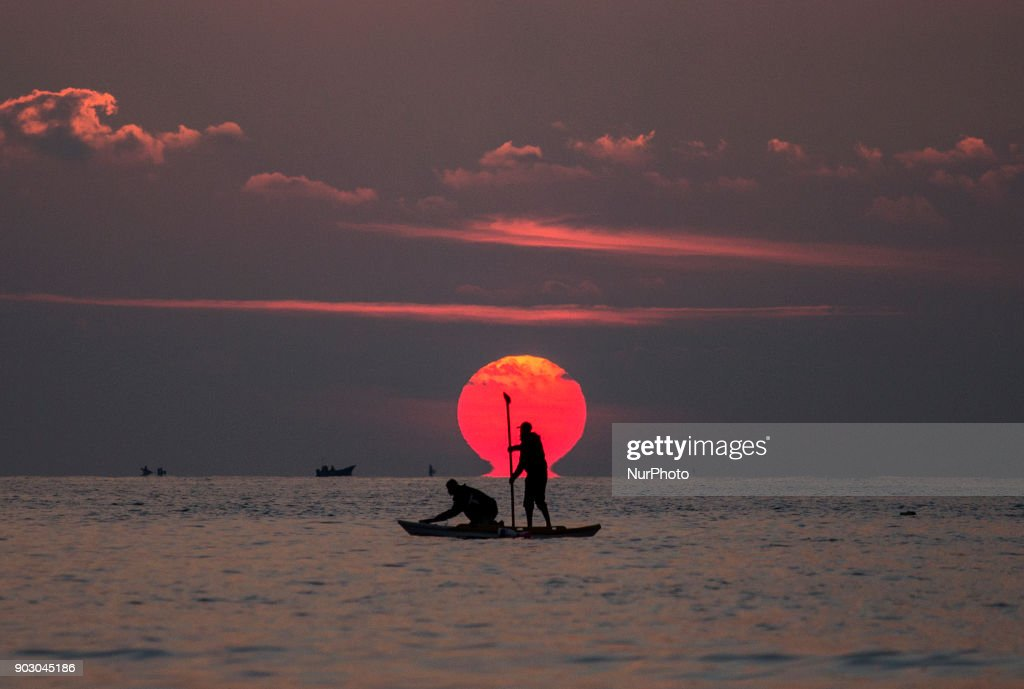 Palestinian fishermen on their boat at sunset off the coast of Gaza City, on January 9, 2018.