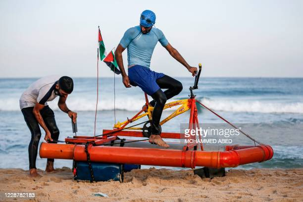 Palestinian fishermen test a custom-built pedal boat made from recycled materials along a beach by Beit Lahia in the northern Gaza Strip on September...