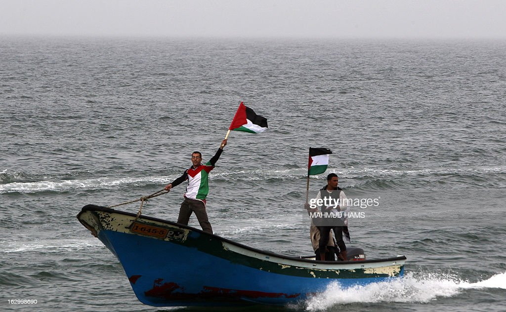 Palestinian fishermen wave their national flag as they ride a boat off the coast of Gaza City during a protest against Israeli military attacks on fishing boats on March 3, 2013. Israel imposes a strict maritime blockade of the Gaza Strip, restricting the access of Palestinian fishermen.