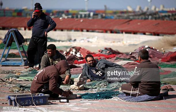 Palestinian fishers prepare their nets for the fishes living in the winter months ahead of sailing in Gaza City Gaza on February 07 2015 Palestinian...