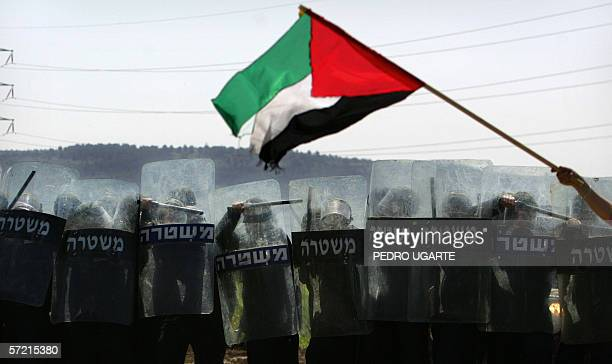 Palestinian flag flutters in the wind in front of a line of Israeli border police as they shield themselves from rocks thrown at them by Palestinian...