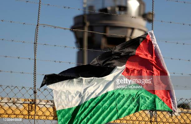 Palestinian flag is pictured on the fence of Israel's Ofer prison near the city of Ramallah in the occupied West Bank, on July 12 during a protest by...