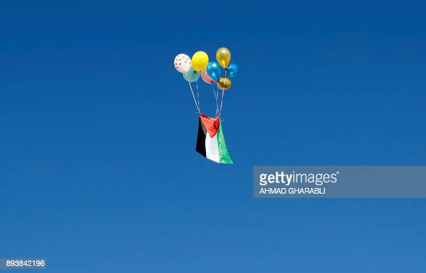 Palestinian flag tied to baloons float away in Jerusalem on December 16 as demonstrations continue to flare in the Middle East and elsewhere over the...