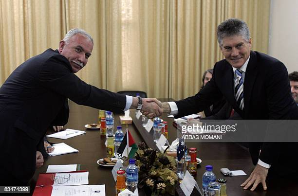 Palestinian Foreign Minister Riyad alMalki shakes hands with his Australian counterpart Stephen Smith during a meeting in the West Bank city of...