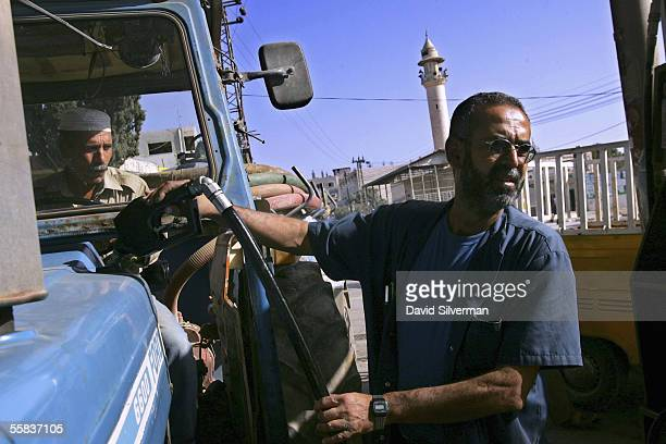 Palestinian gas station attendant Eimad Jallat fills up a Palestinian farmer's tractor with diesel fuel at a gas station October 2 2005 in Hawarra...