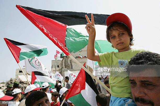 Palestinian girl carried by her father flashes a Vsign as they celebrate at the ElTufah checkpoint near the settlement of Neve Dekalim on August 24...