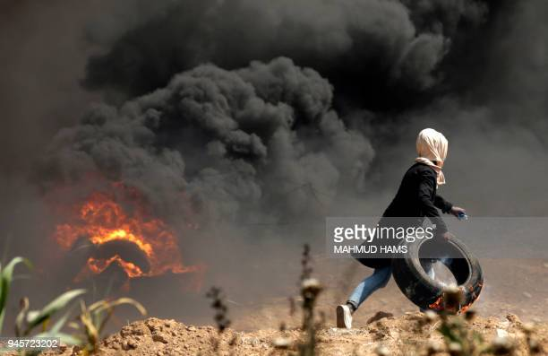A Palestinian girl carries a tire in flames during clashes with Israeli security forces near the Israeli border fence east of Gaza City in the...