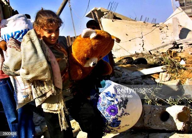 Palestinian girl carries her belongings after her home was destroyed September 16, 2003 in Rafah Refugee Camp, Gaza Strip. Israeli troops demolished...