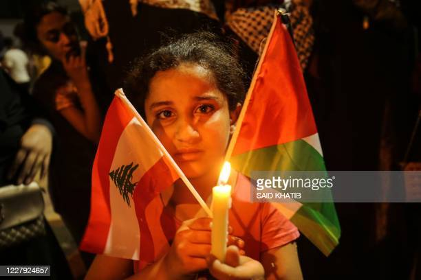 Palestinian girl carries the national flag and the Lebanese flag during a candle light vigil in Rafah in the southern Gaza Strip on August 5 in...
