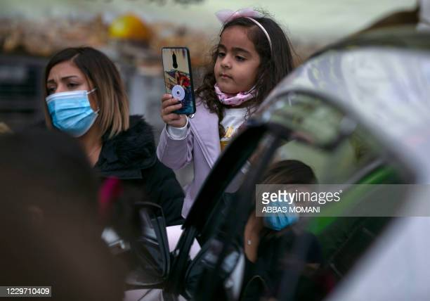 A Palestinian girl checks her phone during a rally in support of 41 women detained in Israeli prisons in the city center of Ramallah in the occupied...