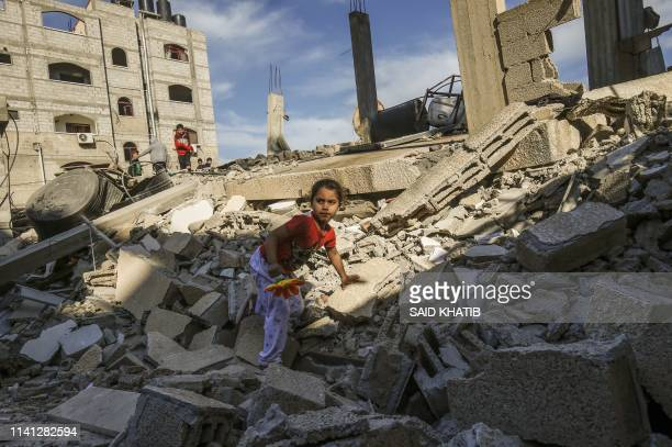 Palestinian girl climbs on the remains of a building that was destroyed during an Israeli air strike on Rafah in the southern Gaza strip on May 5...