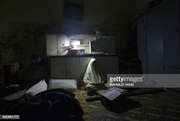 A Palestinian girl does her homework during a power cut in the AlShati refugee camp in Gaza City on January 4 2017 Residents of Gaza home to 18...