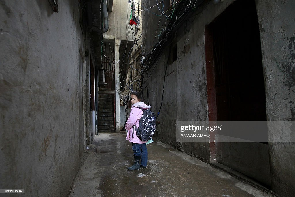 Palestinian girl from the Syrian refugee camp of Yarmuk walks through an alley in the Shatila refugee camp in the Lebanese capital Beirut on December 19, 2012. Some 13,000 members of Syria's Palestinian refugee community have gone back to square one in neighbouring Lebanon. Like their ancestors, they too have been forced to flee their birthplace into exile.