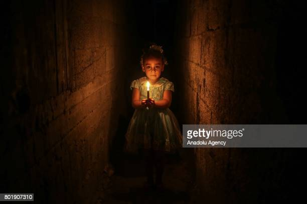 Palestinian girl holds a candle to lighten her home due to power cut at the Jabalia Camp in Gaza City, Gaza on June 27, 2017. 2 million people living...