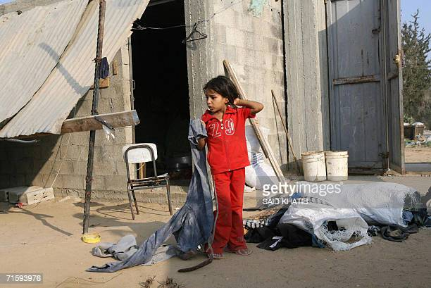 Palestinian girl holds a pair of trousers retrieved from the rubble of her family's destroyed home demolished by Israeli tanks in Rafah town in the...