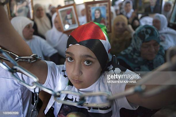 A Palestinian girl holds chains in her hands as she joins fellow women protesting in east Jerusalem on April 15 2010 to demand the release of...