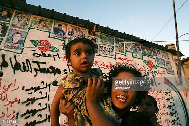 A palestinian girl holds her little sister while she stands in front a wall covered with names and posters of their countrymen martyrs who were...