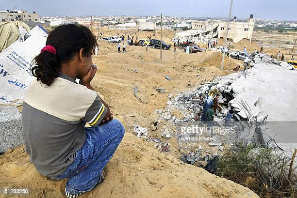 Palestinian girl looks at the remains of destroyed houses after Israeli troops withdrew from the Jabalya refugee camp on September 11 2004 In Gaza...