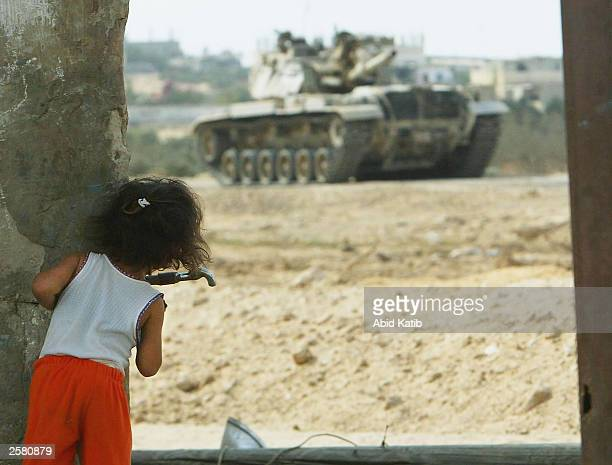 A palestinian girl looks on as an Israeli tank takes position next to Palestinian houses near the Israeli jewish settlement of Murag October 11 2003...