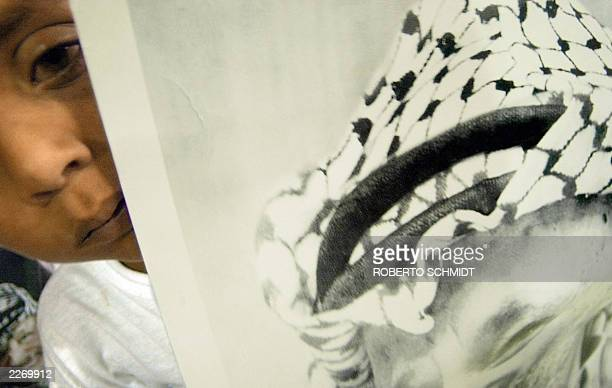 A Palestinian girl peeks from behind a poster of Palestinian leader Yasser Arafat during a demonstration at Gaza International airport 22 June 2003...