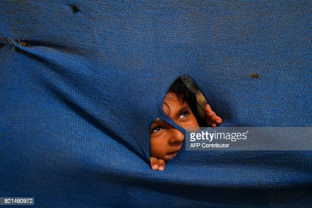 Palestinian girl peers through a tarpaulin next to her house in Gaza City on July 24 2017 / AFP PHOTO / MOHAMMED ABED
