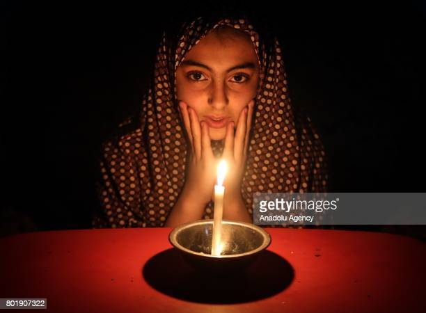 Palestinian girl poses for a photo by candle light due to power cut at the Jabalia Camp in Gaza City Gaza on June 27 2017 2 million people living in...
