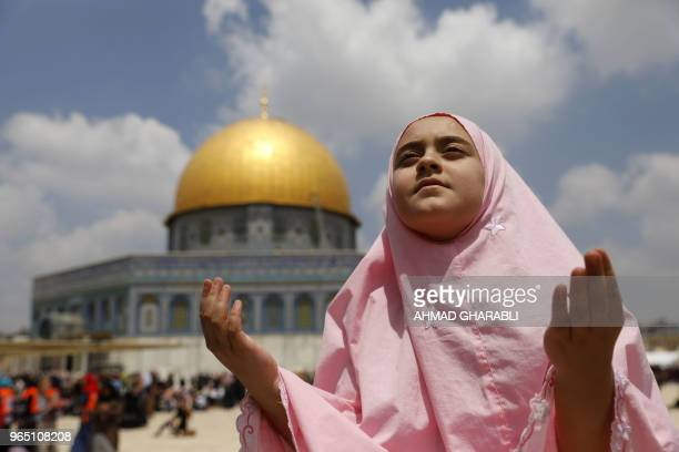 A Palestinian girl prays outside the Dome of the Rock mosque in Jerusalem's AlAqsa Mosque compound on the third Friday prayers of the Muslim holy...