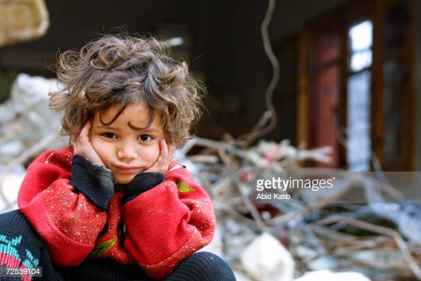 Palestinian girl sits on the rubble of her destroyed home January 16, 2003 in the Rafah Refugee Camp, in southern Gaza Strip. Israeli troops...