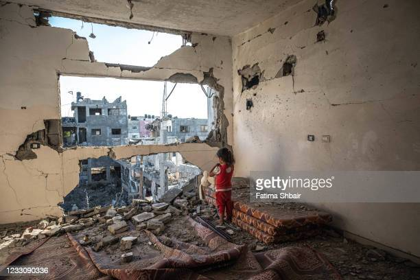Palestinian girl stands amid the rubble of her destroyed home on May 24, 2021 in Beit Hanoun, Gaza. Gaza residents continue clean up operations as...