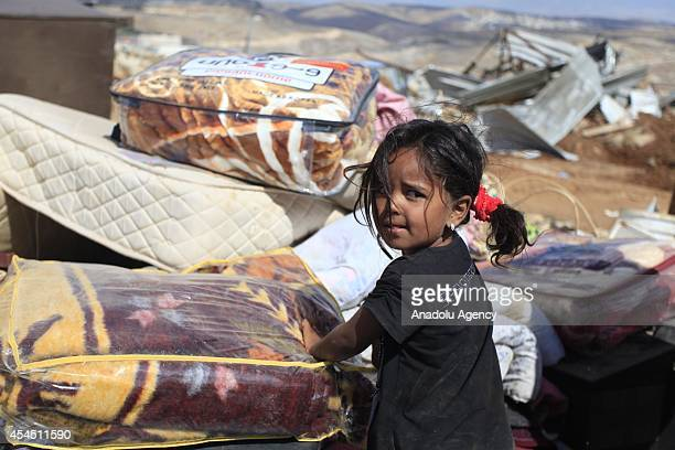 Palestinian girl stands among belongings of her family in the West Bank village of Jabaa near Jenin on September 02 2014 after Israeli troops destroy...