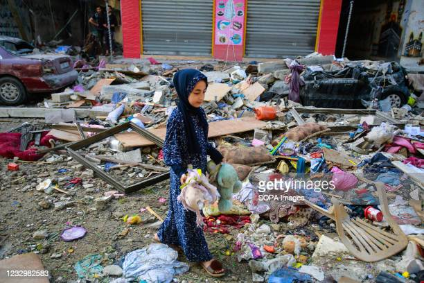 Palestinian girl stands amongst destroyed building to collect her neighbours bears and toys in the aftermath of an Israeli airstrike on Gaza....