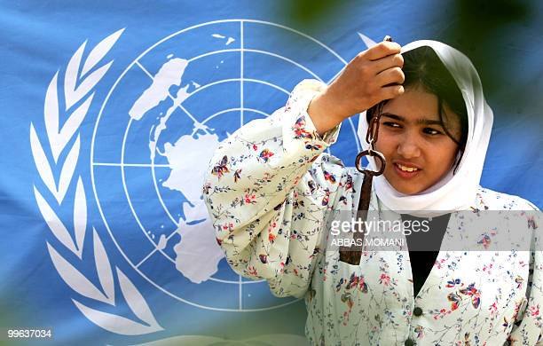 A Palestinian girl stands in front of a United Nations flag as she holdsup a key during a Nakba rally on May 17 2010 in the West Bank village of...