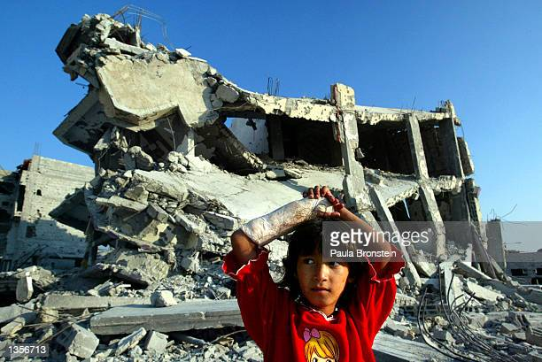 Palestinian girl stands near the rubble of a five-story apartment building August 27, 2002 in the Khan Younis refugee camp in the southern Gaza...