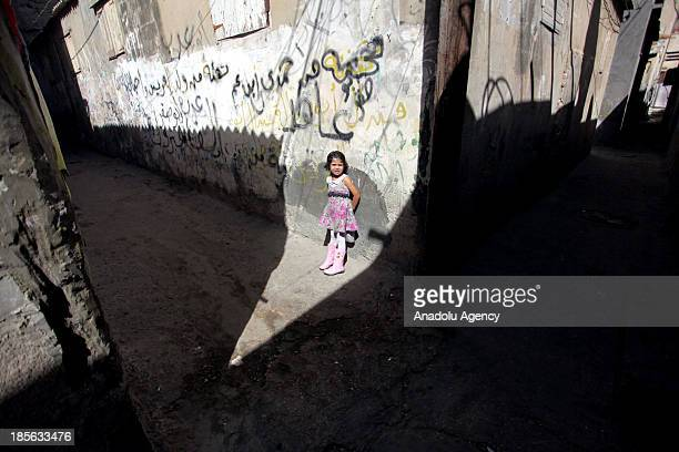 Palestinian girl stands near the wall outside of her family's home at AlShati Palestinian refugee camp the third largest one in the Palestinian...