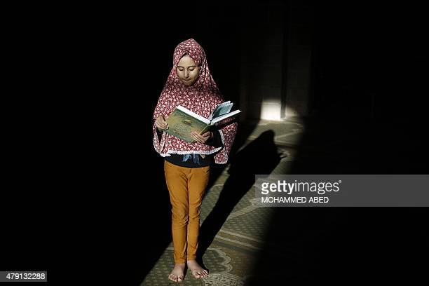 A Palestinian girl stands with a copy of the Koran Islam's holy book at a mosque on the 14th day of the holy fasting month of Ramadan in Gaza City on...