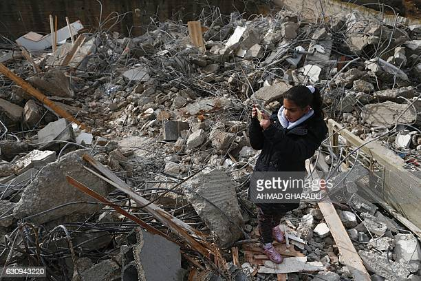 A Palestinian girl takes a picture amid the rubble of a house that was demolished by Israeli army bulldozers in the Arab east Jerusalem neighbourhood...