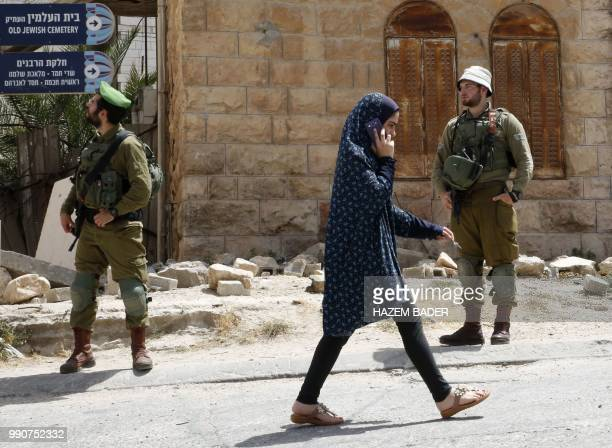 A Palestinian girl talks on her mobile phone passes by Israeli soldiers during a visit by former Israeli soldier Elor Azaria to friends in the...
