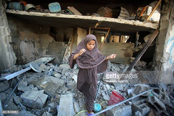 Palestinian girl walks at the site of an Israeli airstrike in Khan Younis southern Gaza Strip on July 8 2014 Seven Palestinians were killed and 25...