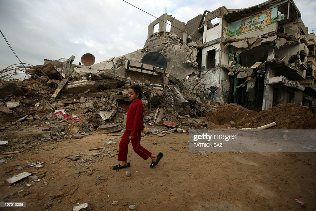 A Palestinian girl walks in the rubble of a house in Gaza City on November 27, 2012.