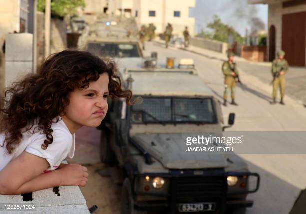 Palestinian girl watches from the balcony of her house as Israeli soldiers conduct a security operation in the village of Aqraba, east of Nablus in...
