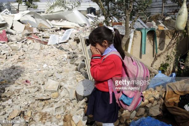 Palestinian girl wearing a school uniform gestures after Israeli forces demolished their house with the claim of being a unauthorized construction in...