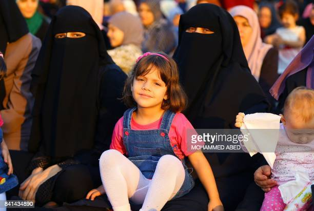 Palestinian girls and women sit at the main square in Gaza City on September 1 2017 after performing the morning prayer for Eid alAdha or the 'Feast...