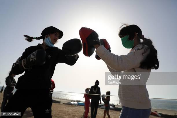 Palestinian girls clad in masks due to the COVID-19 coronavirus pandemic take part in an open-air boxing training near the beach in Gaza City on May...