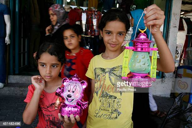 Palestinian girls hold traditional Ramadan lanterns at a market in Rafah in the southern Gaza Strip Starting on Sunday Muslims around the world will...