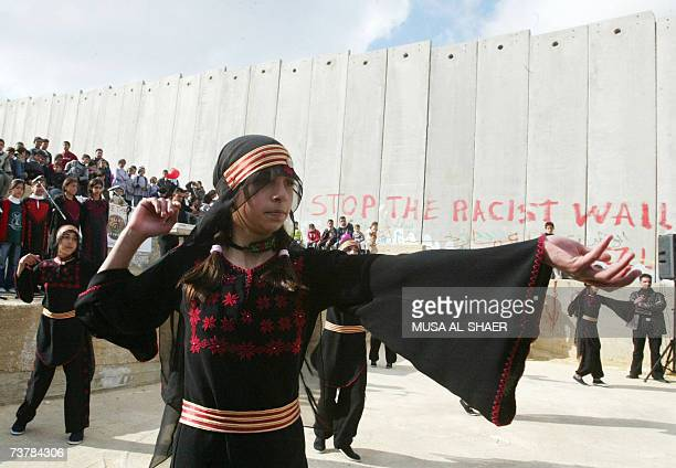 Palestinian girls in traditional costume dance in front of Israel's separation barrier during the DutchPalestine Week in the Aida refugee camp close...