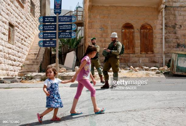 TOPSHOT Palestinian girls pass by Israeli soldiers during a visit by former Israeli soldier Elor Azaria to friends in the settlement of Tal Rumeida...